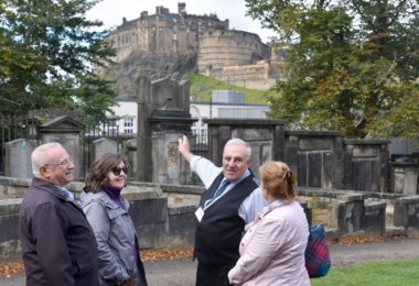 guide showing a group of people the kirkyard