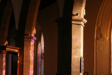 a lovely photo of the interior of Greyfriars Kirk, lit up in colours of the sunset through the stained glass windows