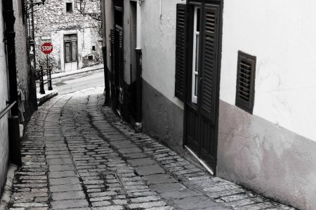 a view of a cobblestone street in black and white, with a red stop sign in the distance